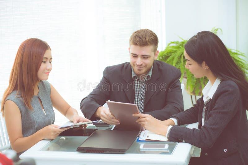 Executivos novos asiáticos que fazem a reunião e que olham a tabuleta para analisar o funcionamento do mercado imagens de stock