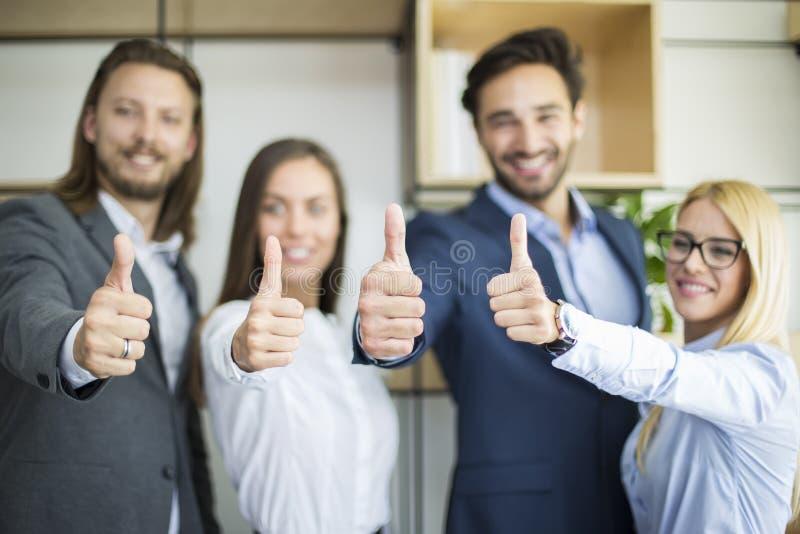 Executivos novos com o polegar acima de estar no escritório imagem de stock