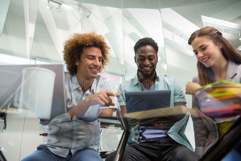 Executivos novos criativos que olham a tabuleta digital fotos de stock royalty free