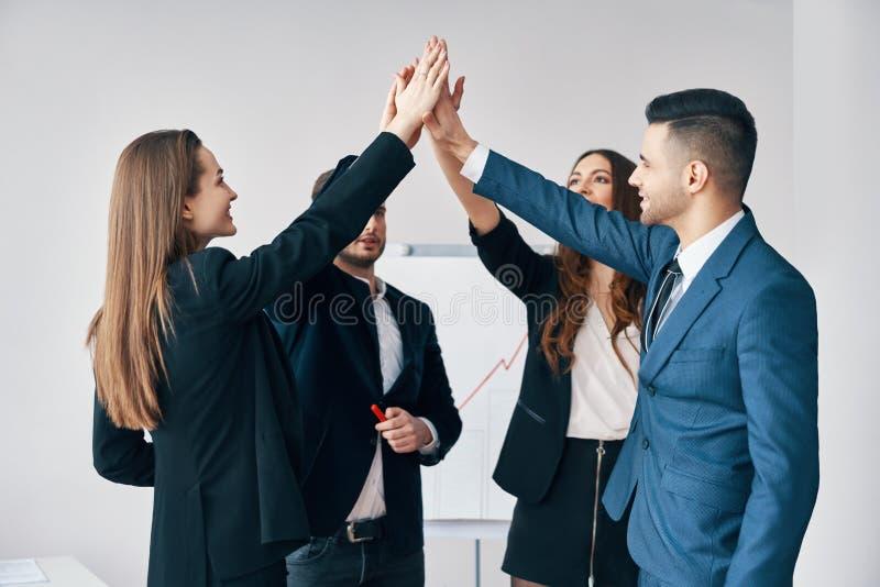 Executivos novos de sorriso que dão cinco altos entre si no escritório fotografia de stock royalty free