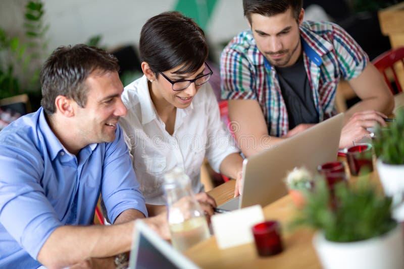 Executivos novos felizes que trabalham na cafetaria fotografia de stock