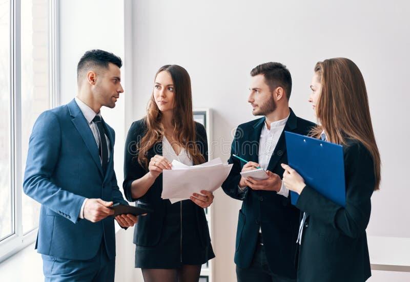 Executivos novos que discutem o projeto novo do negócio no escritório foto de stock