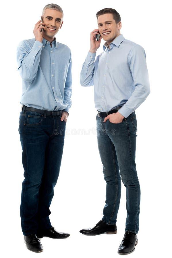Executivos novos que falam através do telefone celular imagens de stock royalty free