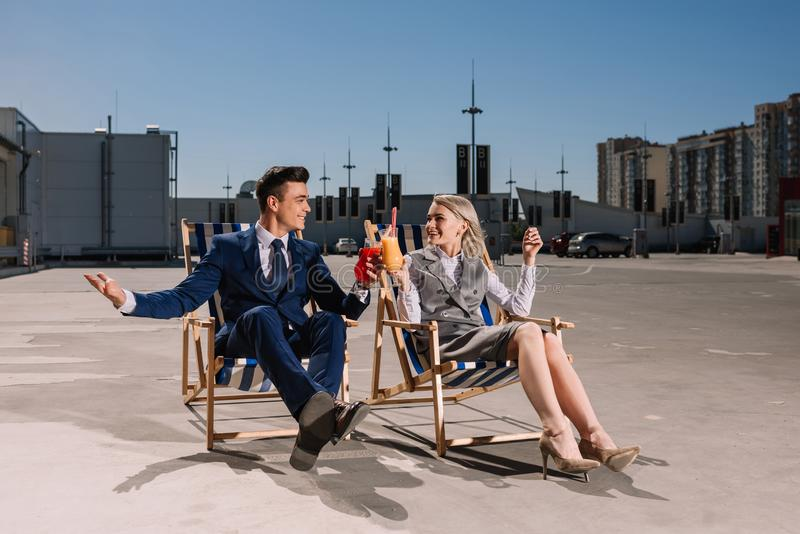 executivos novos que relaxam em vidros do tinido dos sunbeds com cocktail imagem de stock