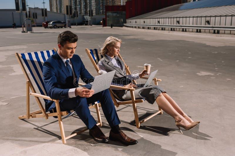 executivos novos que trabalham com portátil ao sentar-se em vadios do sol foto de stock royalty free