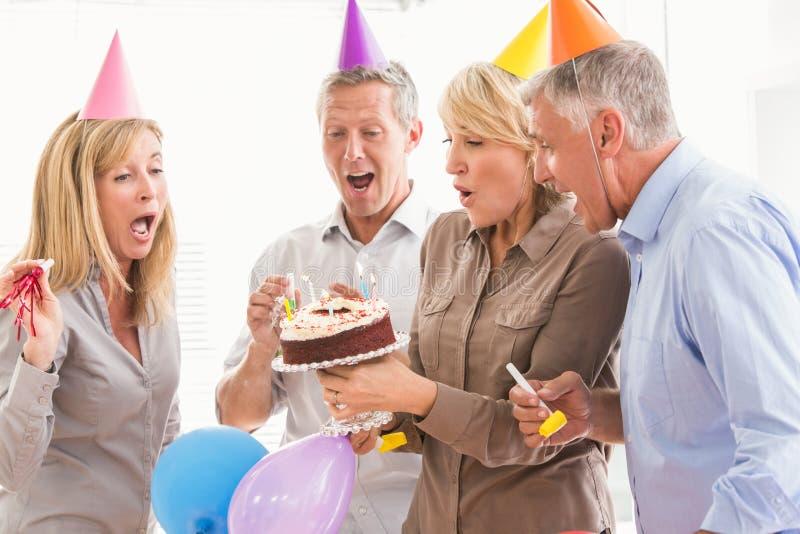 Executivos ocasionais que fundem velas do aniversário foto de stock royalty free