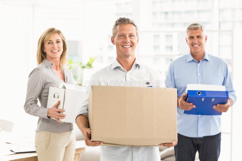 Executivos ocasionais que levam caixas imagens de stock