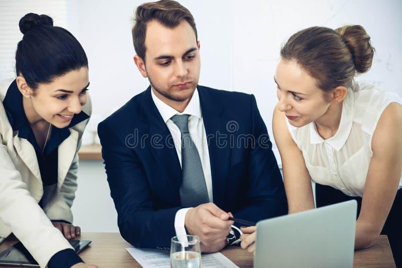 Executivos ou advogados na reuni?o no escrit?rio Focalize em um homem que aponta no port?til imagens de stock