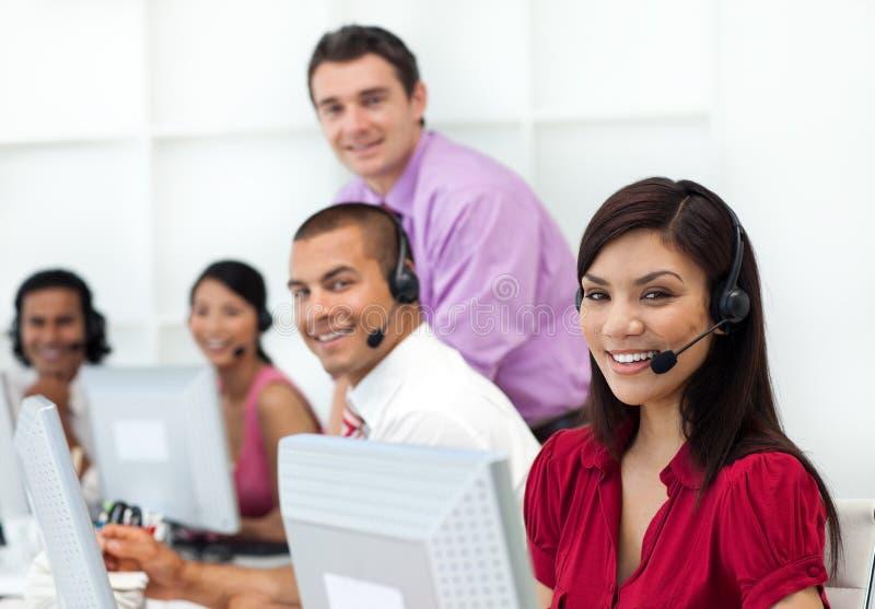 Executivos positivos com os auriculares no trabalho fotos de stock royalty free