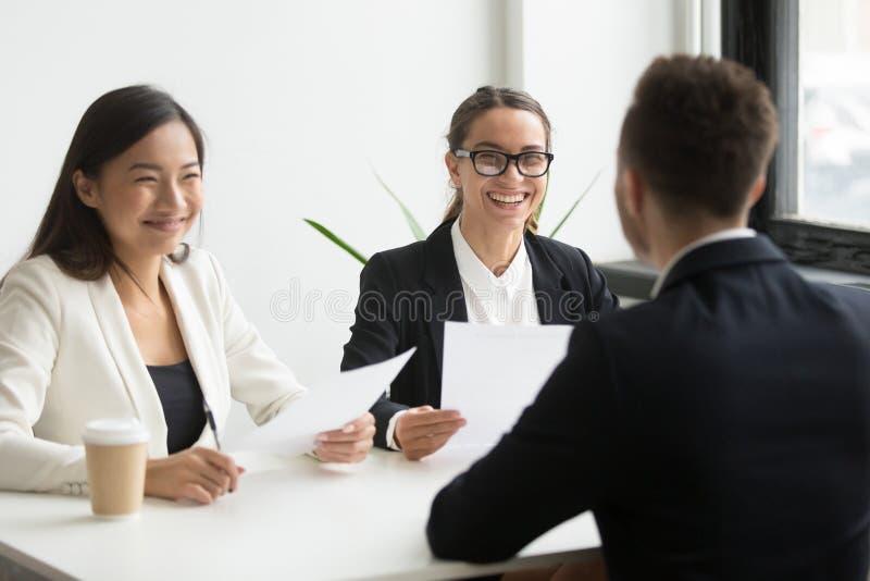 Executivos positivos da hora que riem da entrevista de trabalho com bem sucedido fotografia de stock