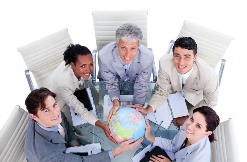 Executivos positivos que prendem um globo fotografia de stock royalty free