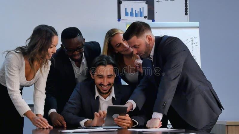Executivos positivos que trabalham com a tabuleta digital no escritório imagem de stock