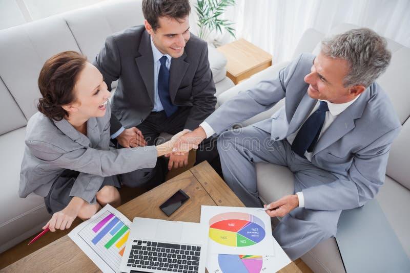 Executivos que agitam as mãos ao trabalhar imagens de stock