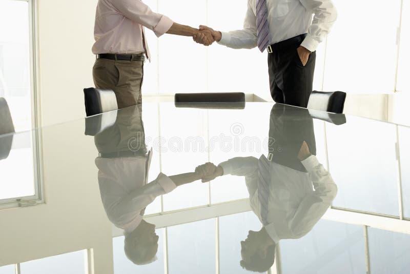 Executivos que agitam as mãos na sala de conferências fotografia de stock
