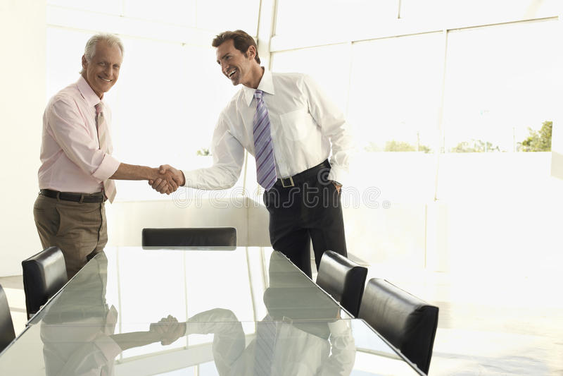 Executivos que agitam as mãos na sala de conferências imagem de stock royalty free