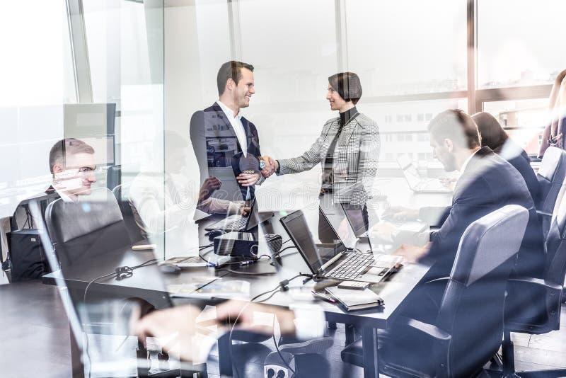 Executivos que agitam as mãos no escritório empresarial do moder imagem de stock