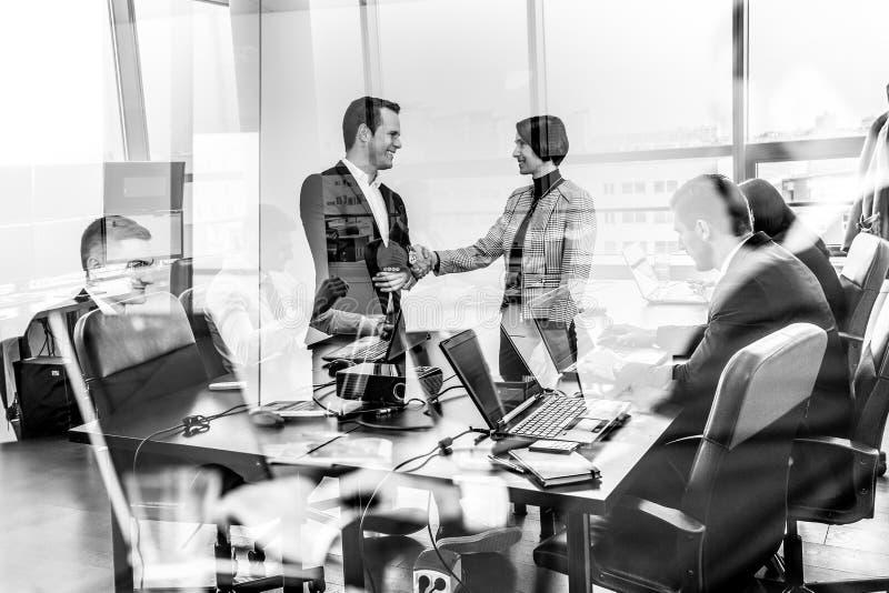 Executivos que agitam as mãos no escritório empresarial do moder fotos de stock
