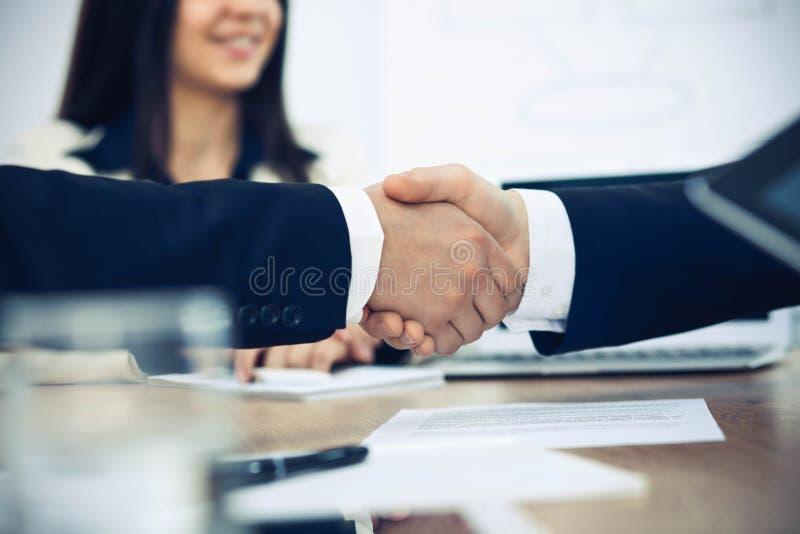Executivos que agitam as m?os no encontro ou na negocia??o no escrit?rio Conceito do aperto de m?o Os s?cios s?o satisfeitos porq imagem de stock