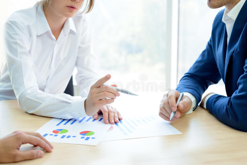 Executivos que analisam resultados financeiros em gráficos em torno da tabela no escritório moderno Conceito do trabalho da equip foto de stock royalty free