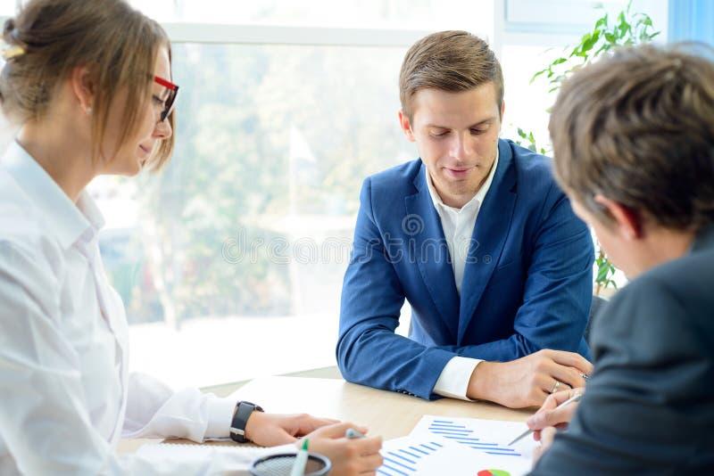 Executivos que analisam resultados financeiros em gráficos em torno da tabela no escritório moderno Conceito do trabalho da equip imagens de stock royalty free