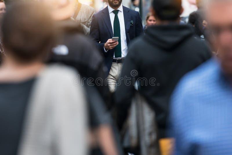 Executivos que andam do trabalho na rua ocupada da cidade imagem de stock