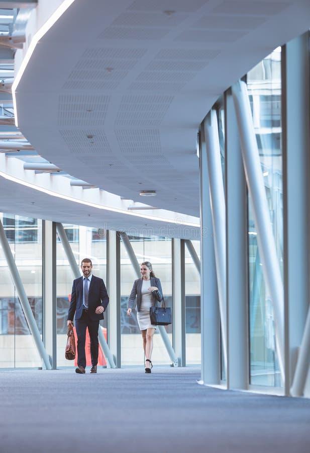 Executivos que andam junto no corredor no prédio de escritórios moderno imagens de stock