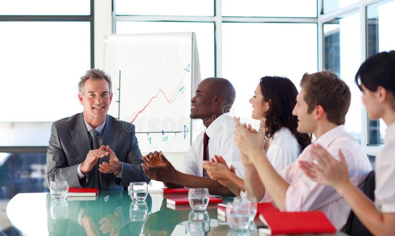 Executivos que aplaudem em uma reunião fotos de stock