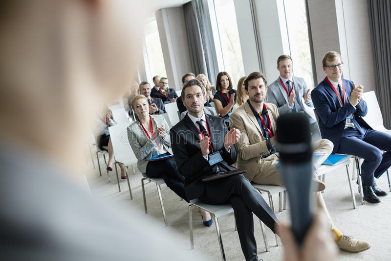 Executivos que aplaudem para o orador público durante o seminário no centro de convenções fotos de stock