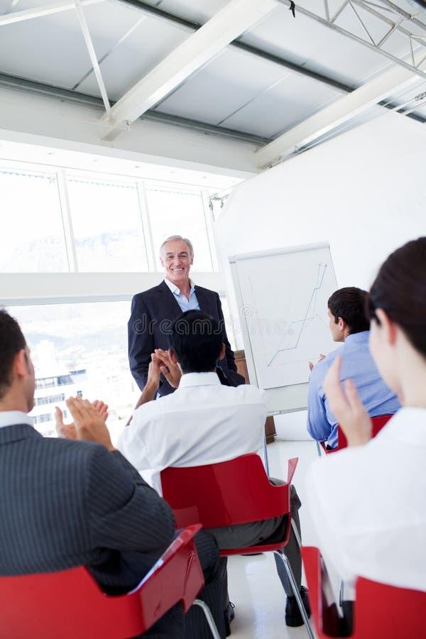 Executivos que aplaudem uma conferência imagem de stock