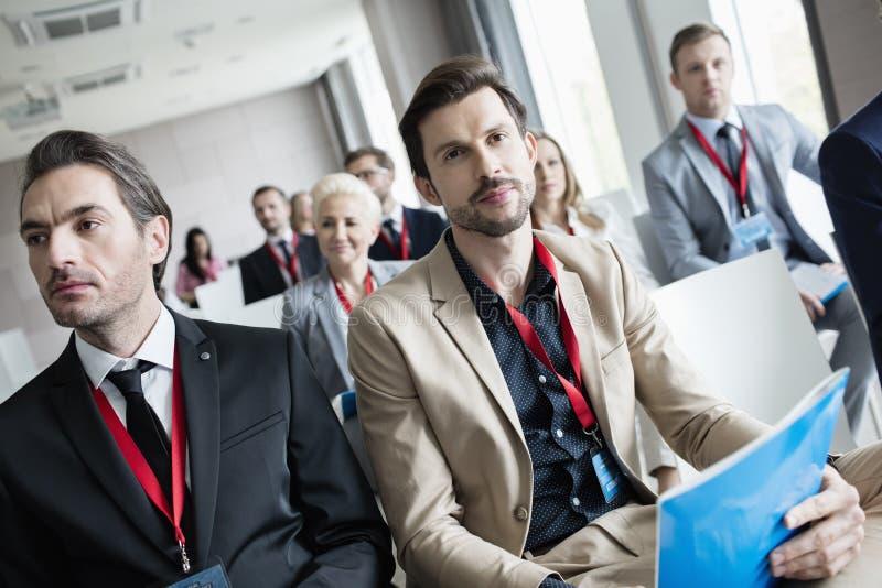 Executivos que atendem ao seminário no centro de convenções fotos de stock royalty free