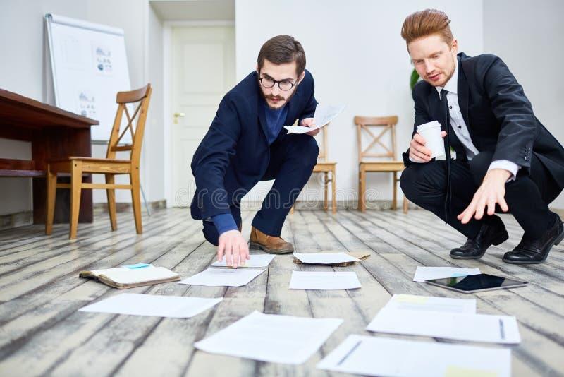 Executivos que classificam a documentação no assoalho foto de stock