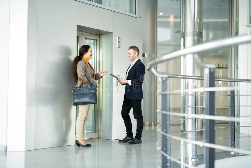Executivos que conversam pelo elevador imagem de stock