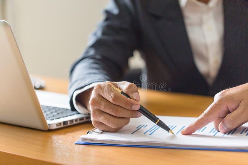 Executivos que discutem as cartas e os gráficos que mostram o res foto de stock