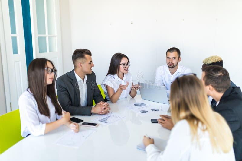 Executivos que discutem as cartas e os gráficos que mostram os resultados de seus trabalhos de equipa bem sucedidos, multi negóci imagem de stock