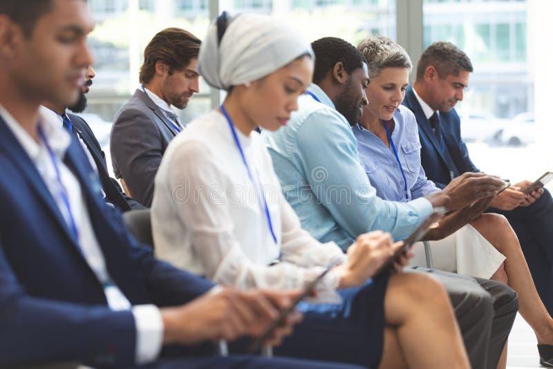 Executivos que discutem sobre a tabuleta digital durante o seminário foto de stock