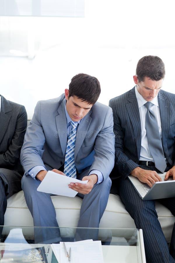 Executivos que esperam um trabalho inter imagens de stock