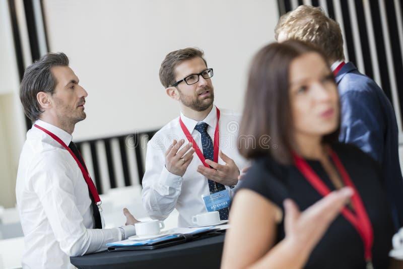 Executivos que falam durante a ruptura de café no centro de convenções foto de stock
