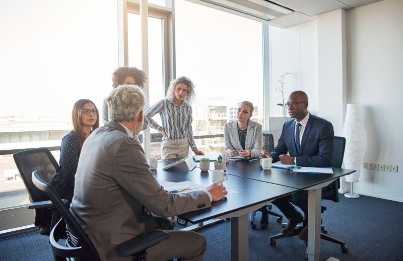 Executivos que falam o negócio junto em uma sala de reuniões do escritório imagens de stock royalty free
