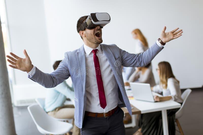 Executivos que fazem o exercício de formação da equipe durante o seminário do desenvolvimento de equipas usando vidros de VR imagem de stock royalty free