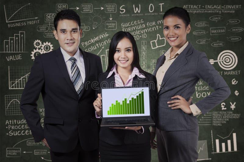 Executivos que guardam o gráfico do crescimento imagens de stock royalty free