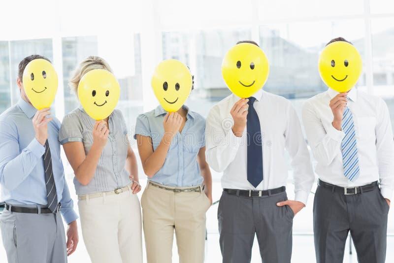 Executivos que guardam sorrisos felizes na frente das caras imagens de stock