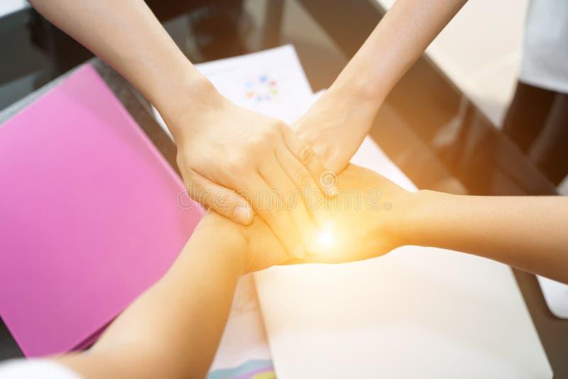 Executivos que juntam-se às mãos junto colega que guarda as mãos imagem de stock