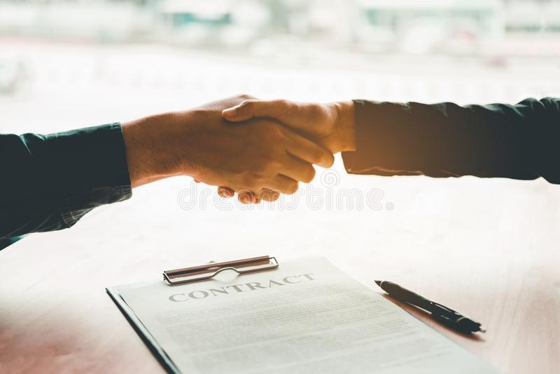 Executivos que negociam um aperto de mão do contrato entre o colo dois
