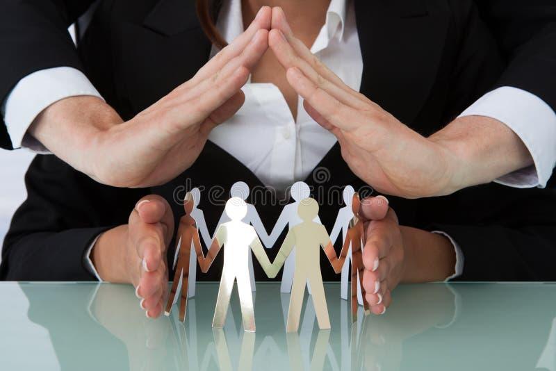 Executivos que protegem a equipe dos povos de papel na mesa foto de stock