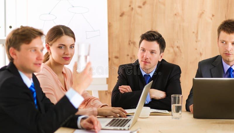 Executivos que sentam-se e que discutem na reunião de negócios, no escritório foto de stock
