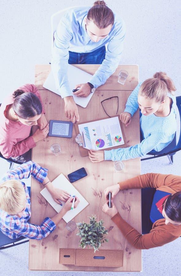Executivos que sentam-se e que discutem na reunião, no escritório imagens de stock