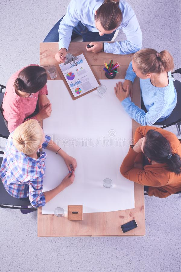 Executivos que sentam-se e que discutem na reuni?o, no escrit?rio foto de stock