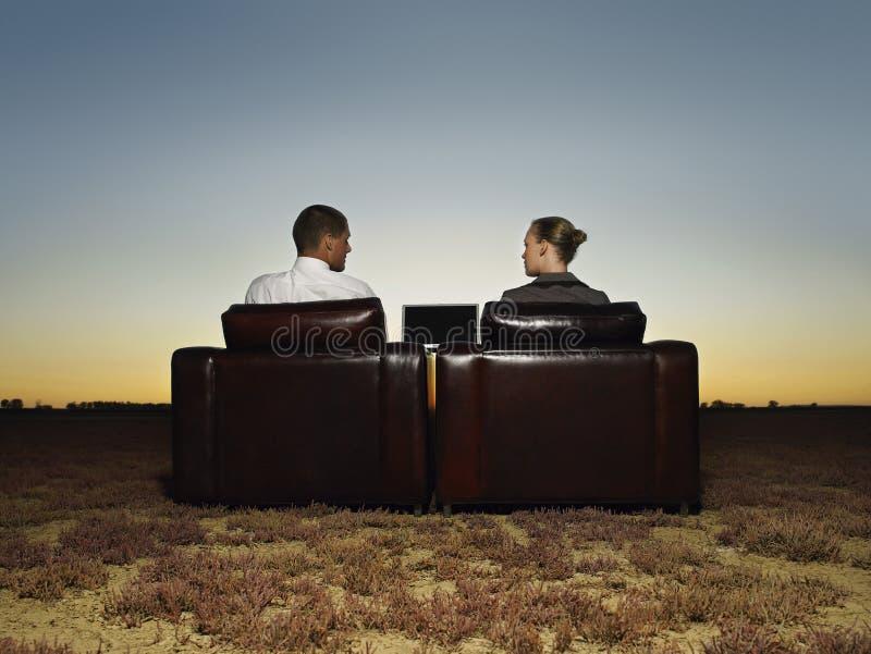 Executivos que sentam-se em poltronas com portátil imagem de stock