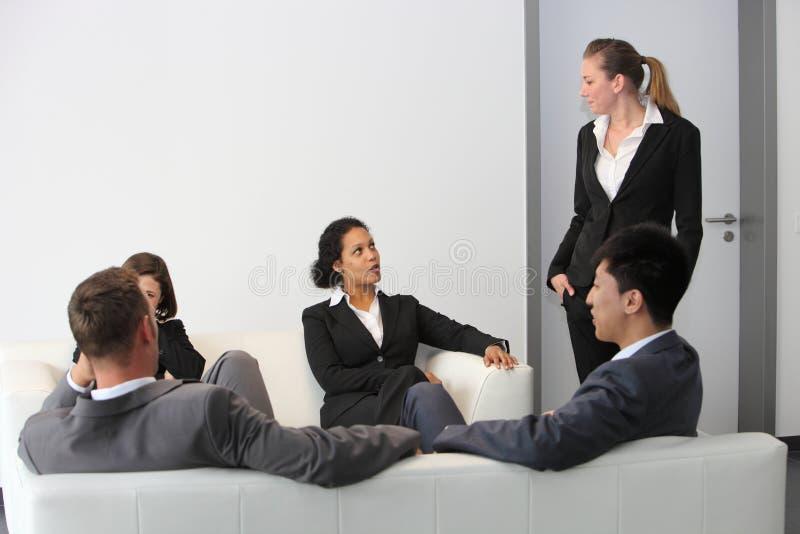 Executivos que sentam-se em uma sala de espera imagens de stock