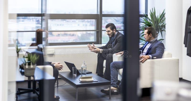 Executivos que sentam-se na reunião de funcionamento no escritório empresarial moderno imagem de stock